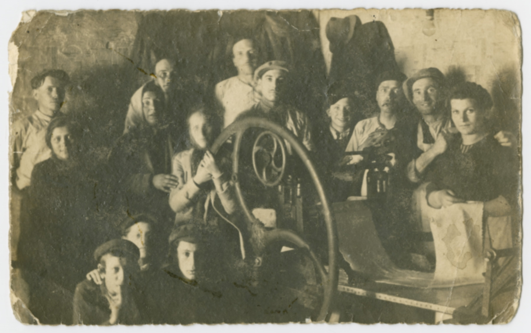 Group portrait of workers in a matzah factory.  Sandor Grunspan (uncle of the donor) is pictured in the center.  He died one week after liberation.