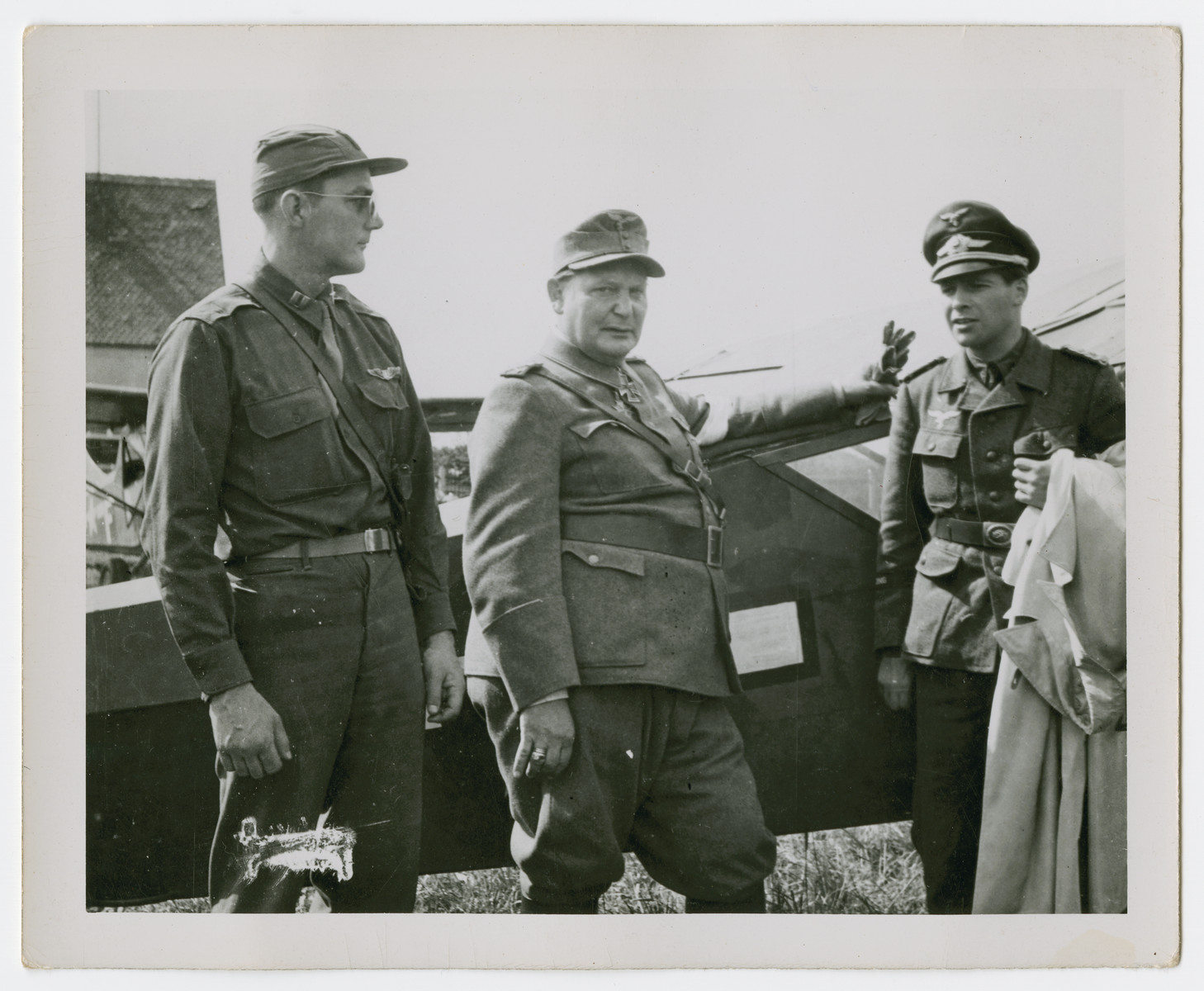 Herman Goering and his adjutant stand next to an airplane accompanied by an American soldier shortly after his capture.
