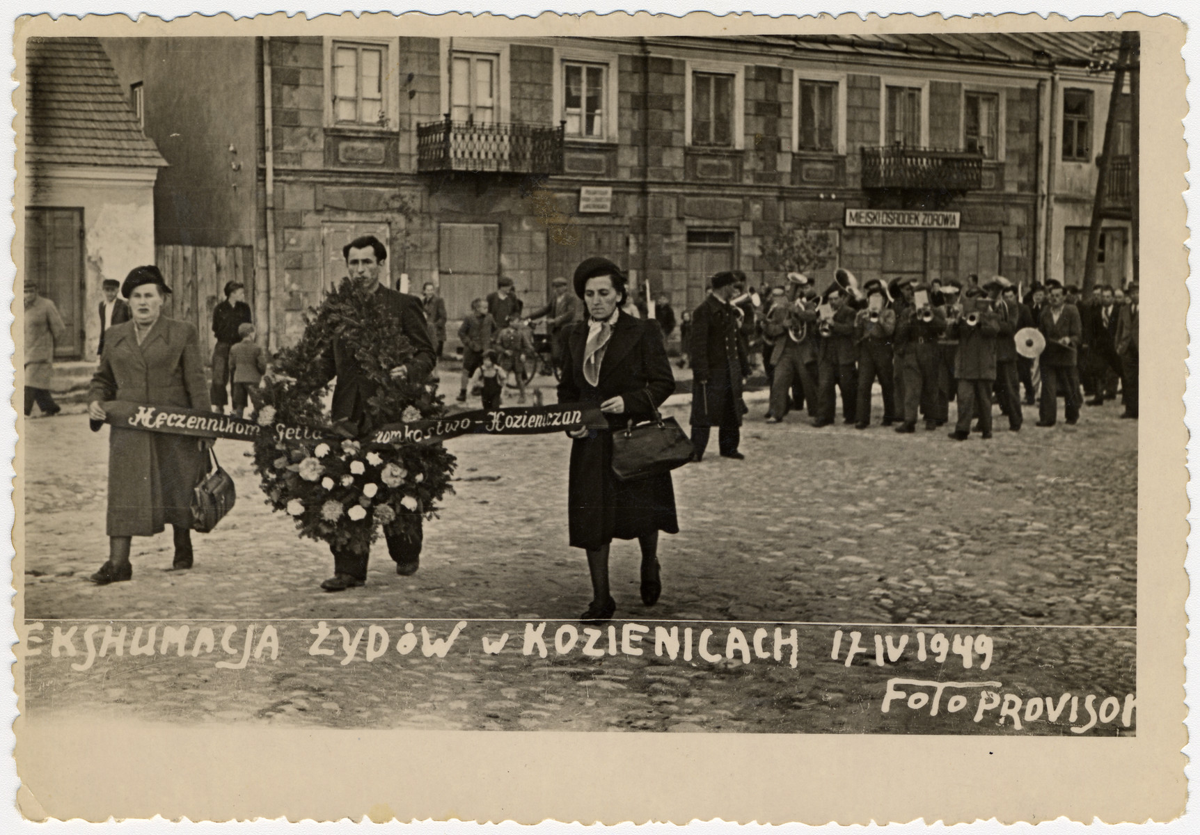 Survivors carrying a wreath and banner march in a funeral procession during the exhumation and reburial ceremony in Kozienice of Nazi victims.