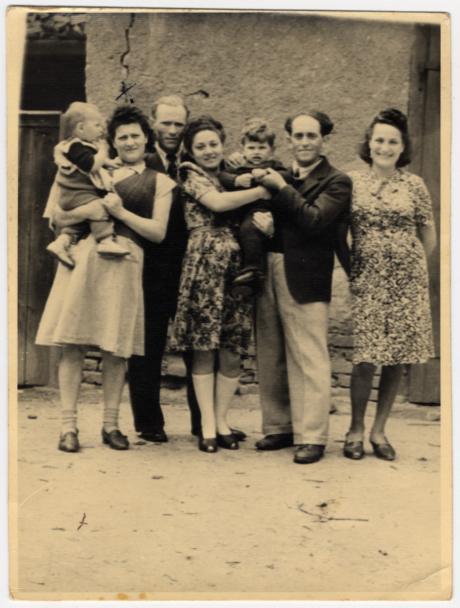 Portrait of five displaced persons holding two young children.