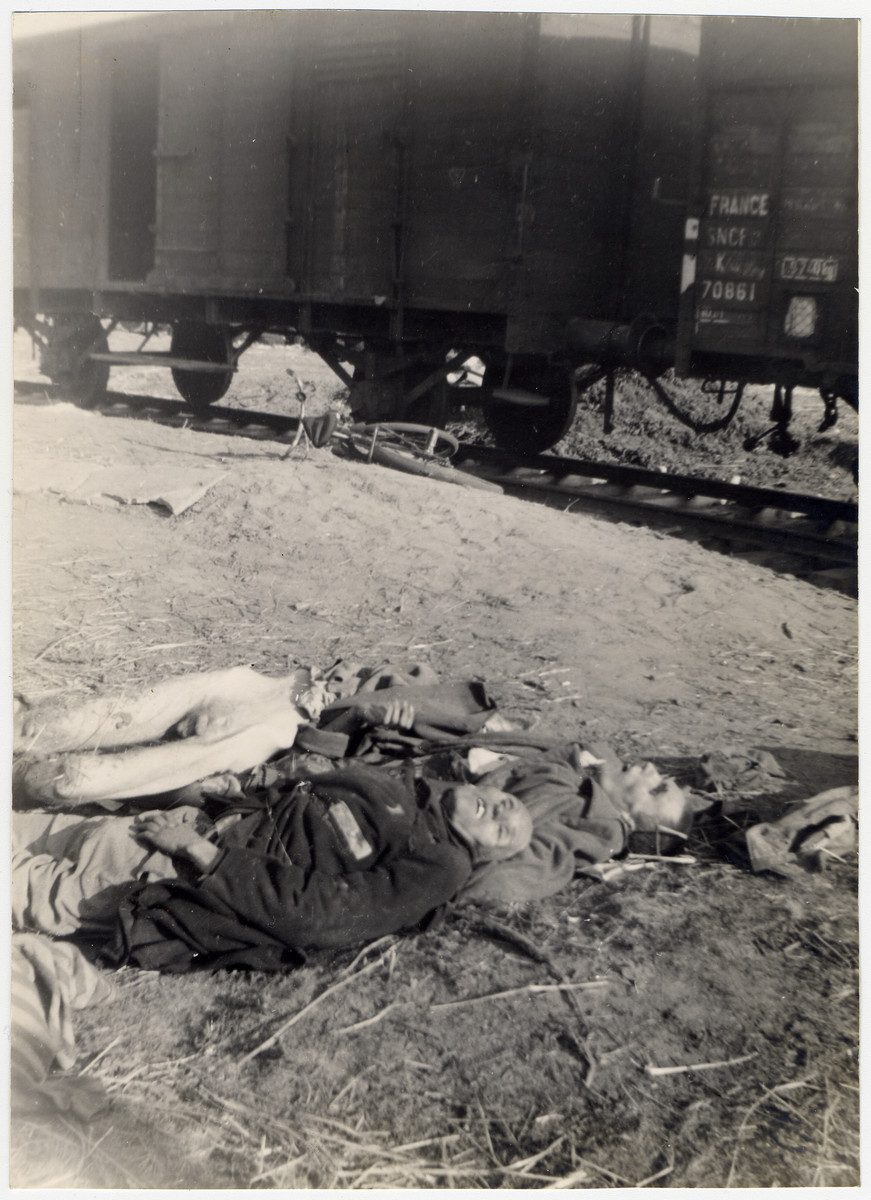 Two corpses [possible of SS men] lie next to a train in either Dachau or Woebbelin concentration camp.  [This photograph was included in a series of photographs of the liberation of Woebbelin, but it more closely resembles photos of the Dachau death train.]
