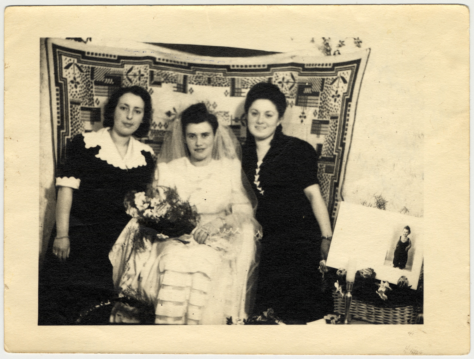 """Two women sit in attendance with a bride.    Shulamit Perlmutter is seated on the far right.  The original caption reads """"To the nice Musia, as an eternal memento, I give you this picture.  Moniek and Hanka""""."""