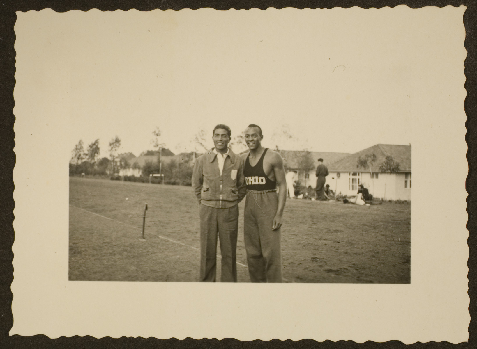 Jesse Owens, American track-and-field Olympic athlete, wearing his Ohio State University track suit, poses with another gentleman.