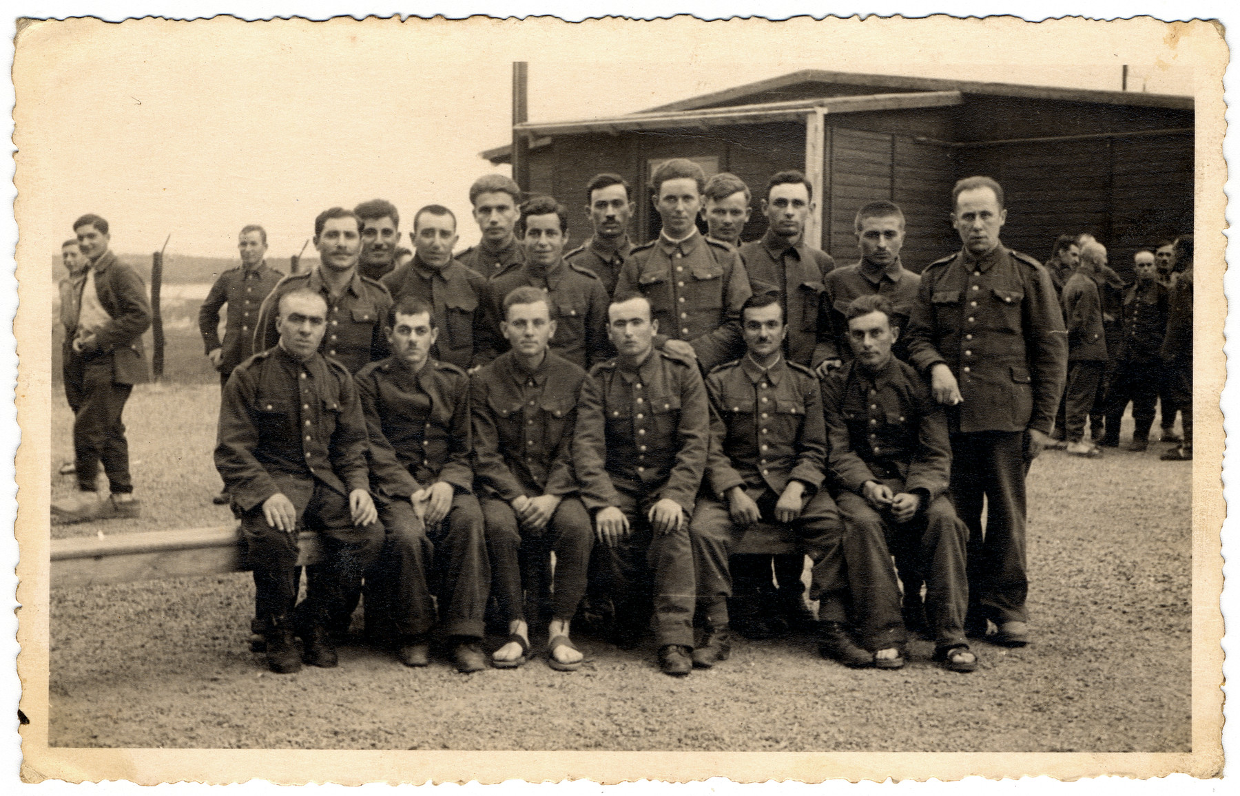 Group portrait of prisoners in the Elsterhorst prisoner of war camp, Stalag IV-A.  Jan Szelubski is pictured standing, fifth from the left. Rio Francis is pictured sitting, first on right.