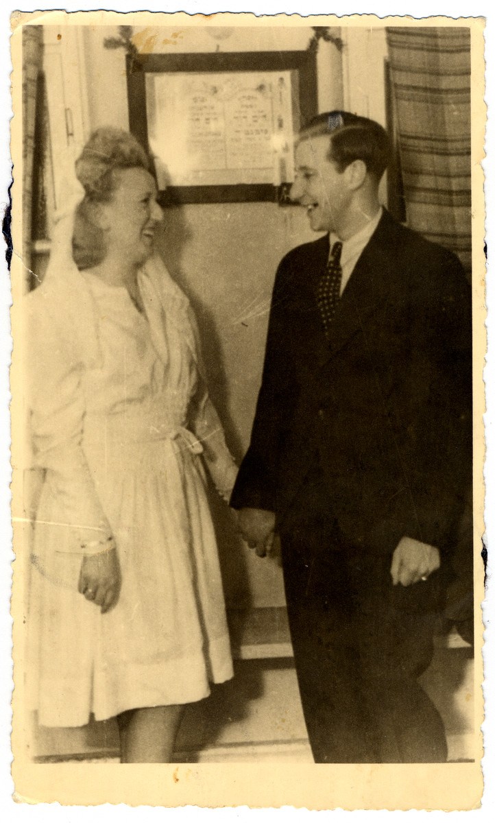 Ruth and Harry Posmantier look at one another on their wedding day.  They are standing in front of his father's memorial.