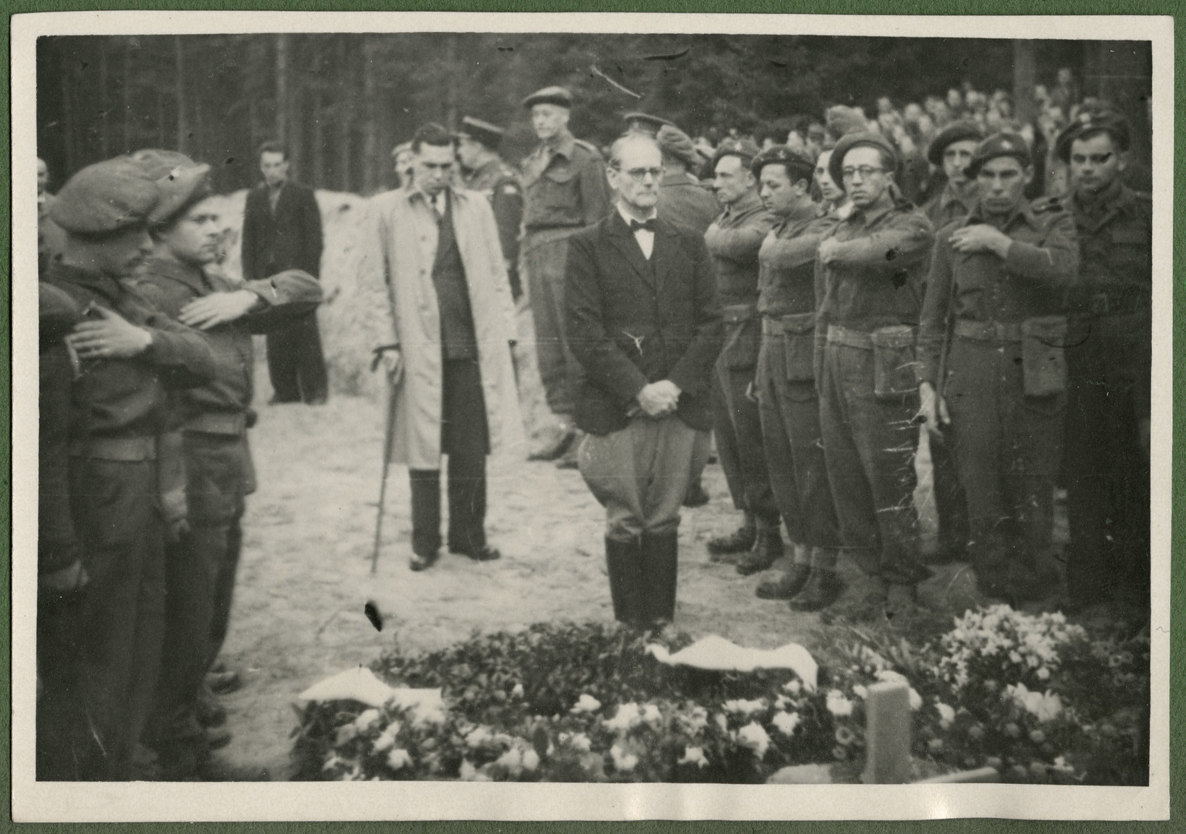 Belgian soldiers and the major of Lueneburg pay their final respects to the 243 slave laborers who were shot by their guards on the railway lines at Lueneburg on the way to the Belsen Camp.