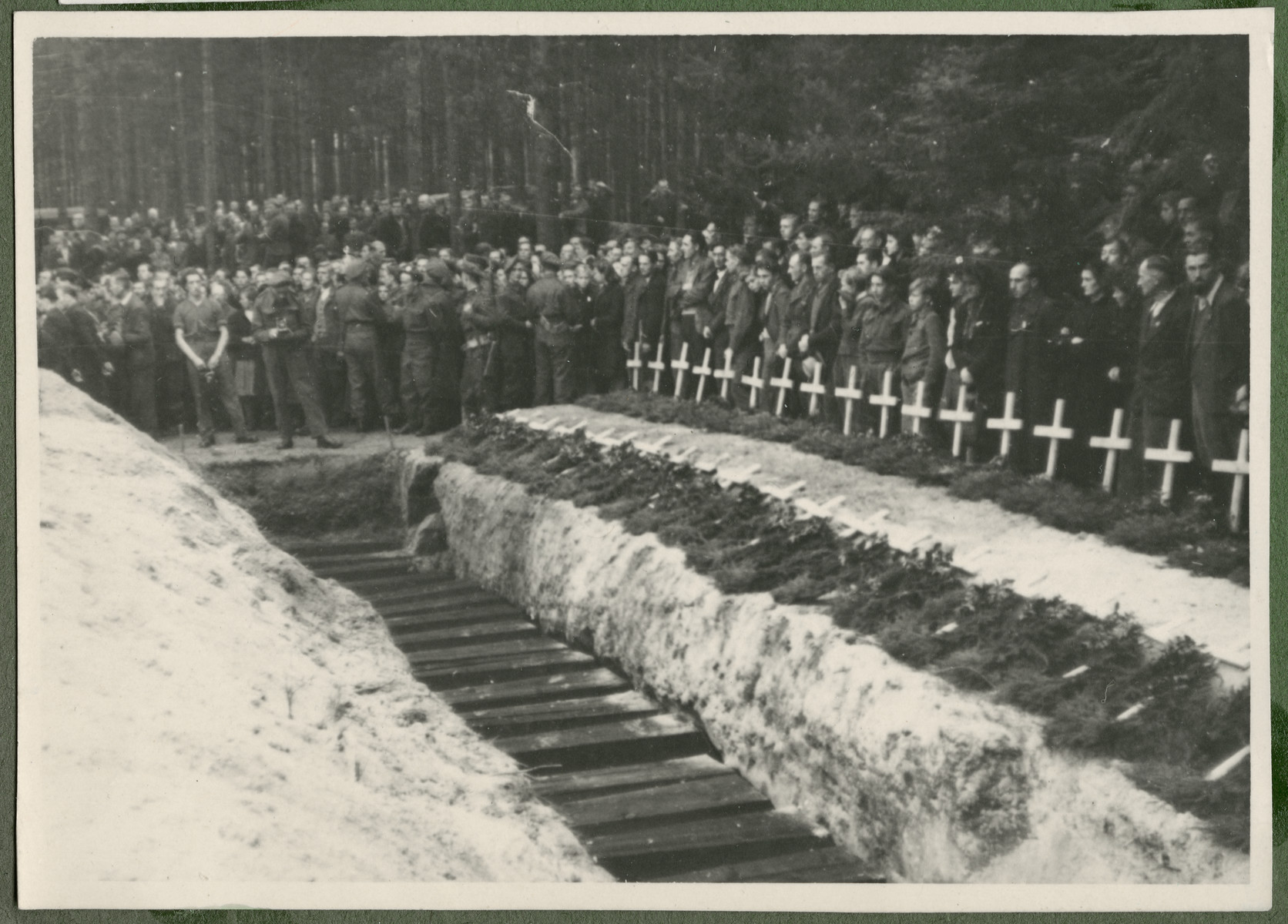 Under the supervision of British troops, German civilians and Nazi officials pay hommage to the graves of 243 slave laborers who were shot by their guards on the railway lines at Lueneberg on the way to the Belsen Camp.