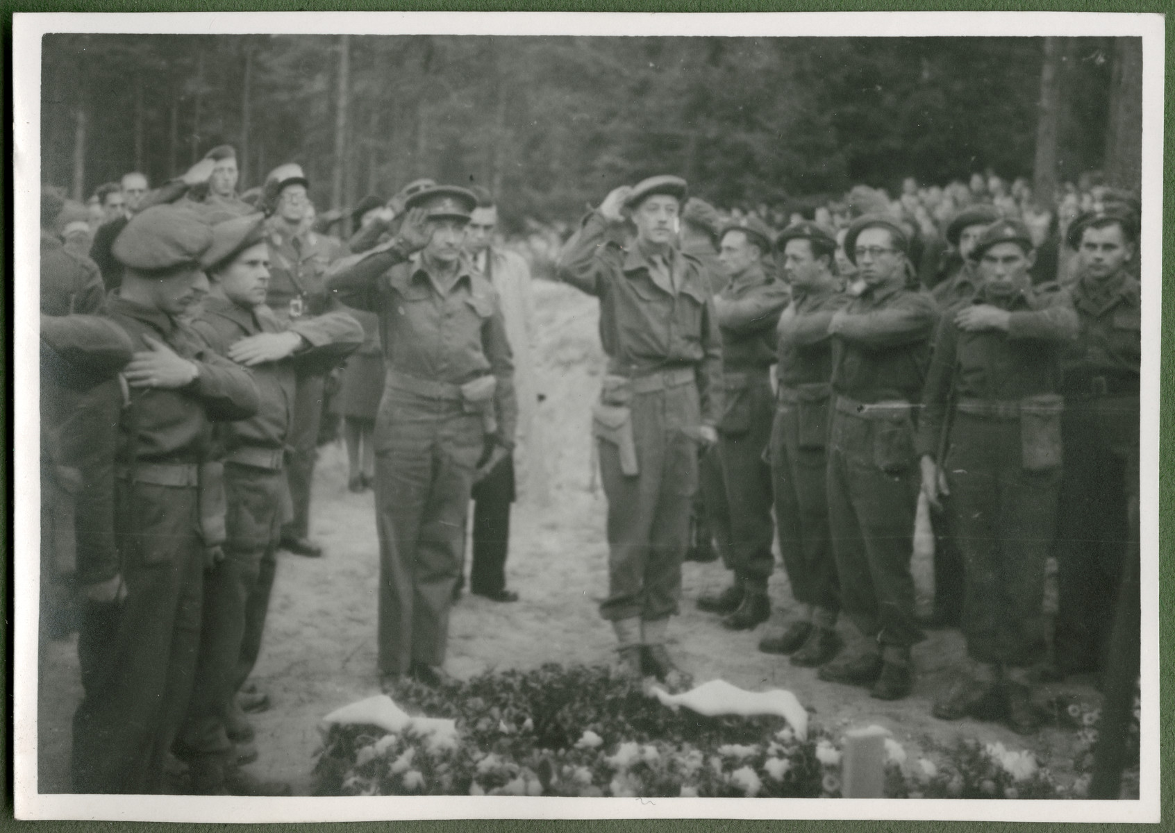 "Belgian and British soldiers pay their lfinal respects to the 243 slave laborers who were shot by their guards on the railway lines at Lueneburg on the way to the Belsen Camp.   The original caption reads: ""The last salute to the 243 martyrs.""  Marcel Frank is soluting in the center, left."