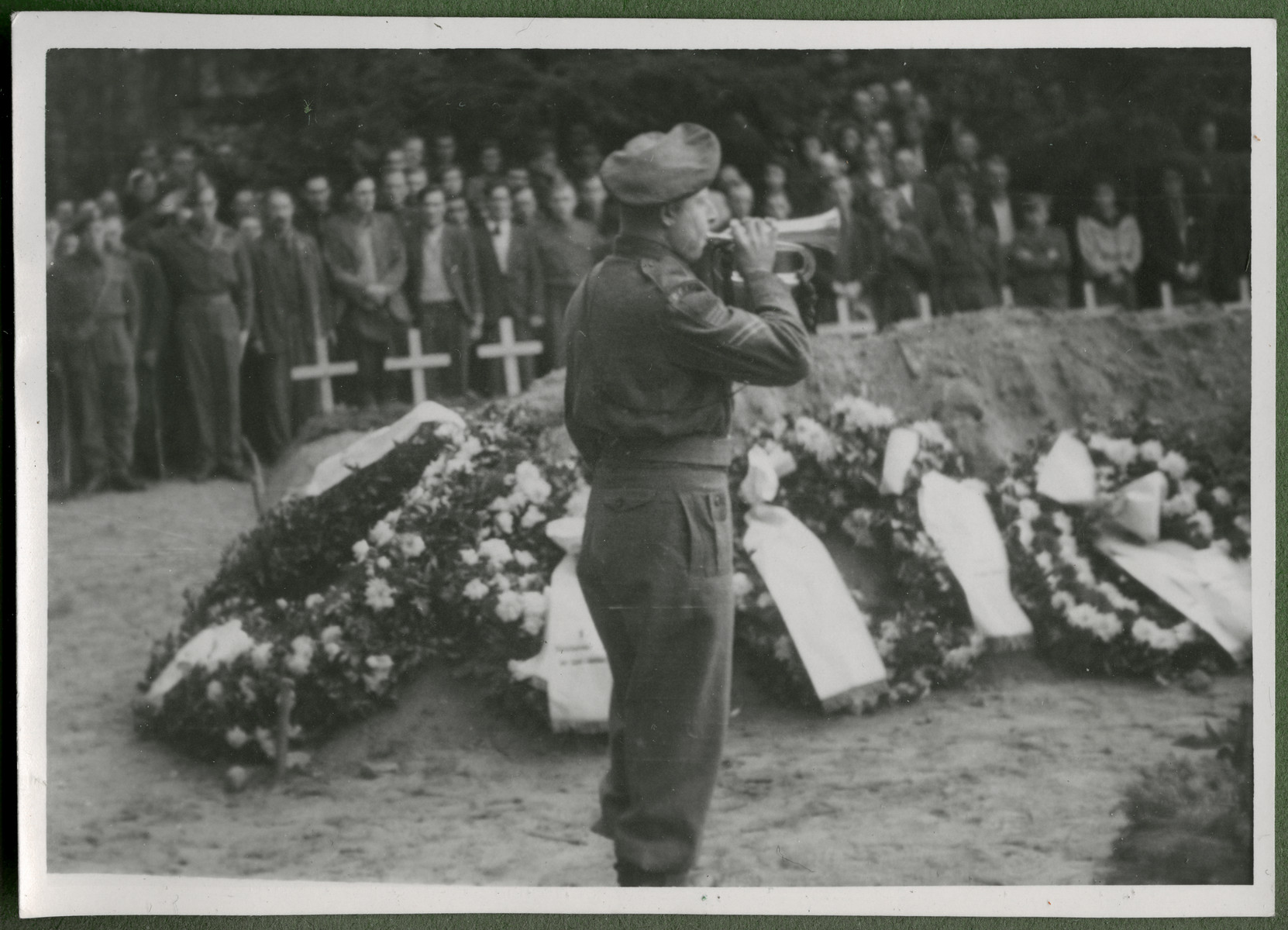 A bugler plays taps at a memorial service for the 243 slave laborers who were shot by their guards on the railway lines at Lueneburg on the way to the Belsen Camp.