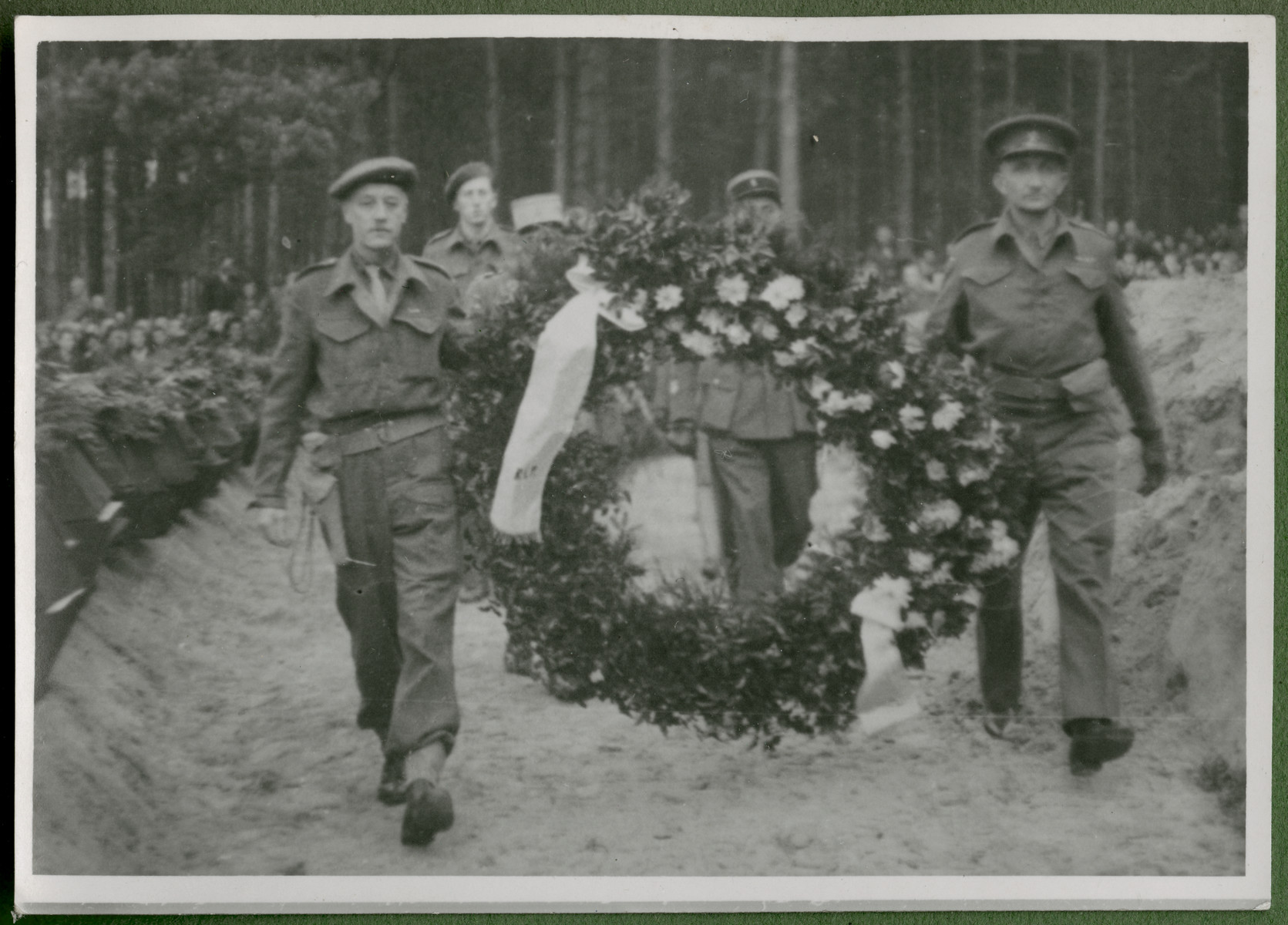 Major Shipway and Lt. Marcel Frank carry a large floral wreath to the mass grave of 243 slave laborers who were shot by their guards on the railway lines at Lueneburg on the way to the Belsen Camp.