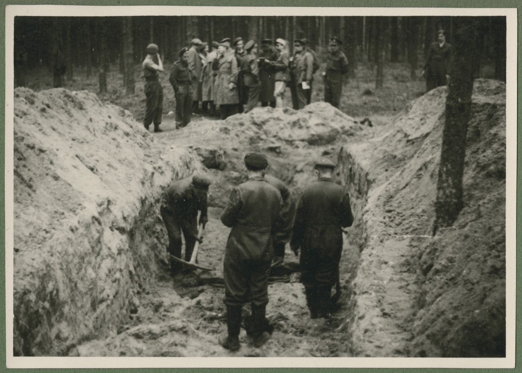Under the supervision of British troops, German civilians and Nazi officials exhume the corpses of 243 slave laborers for proper reburial.  The victims were shot by their guards on the railway lines at Lueneberg on the way to the Belsen Camp.
