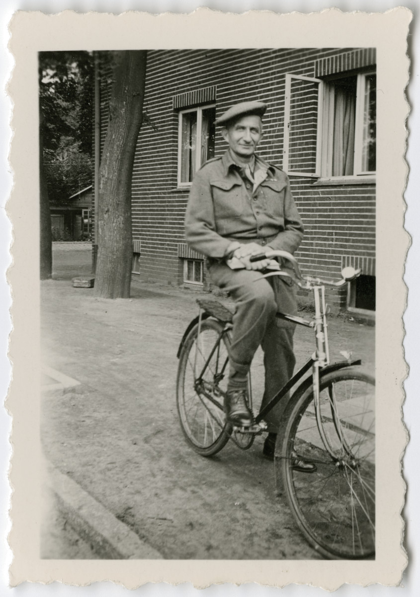 Close-up portrait of Lt. Marcel Frank riding a bicycle, a Belgian liaison officer with the British army.