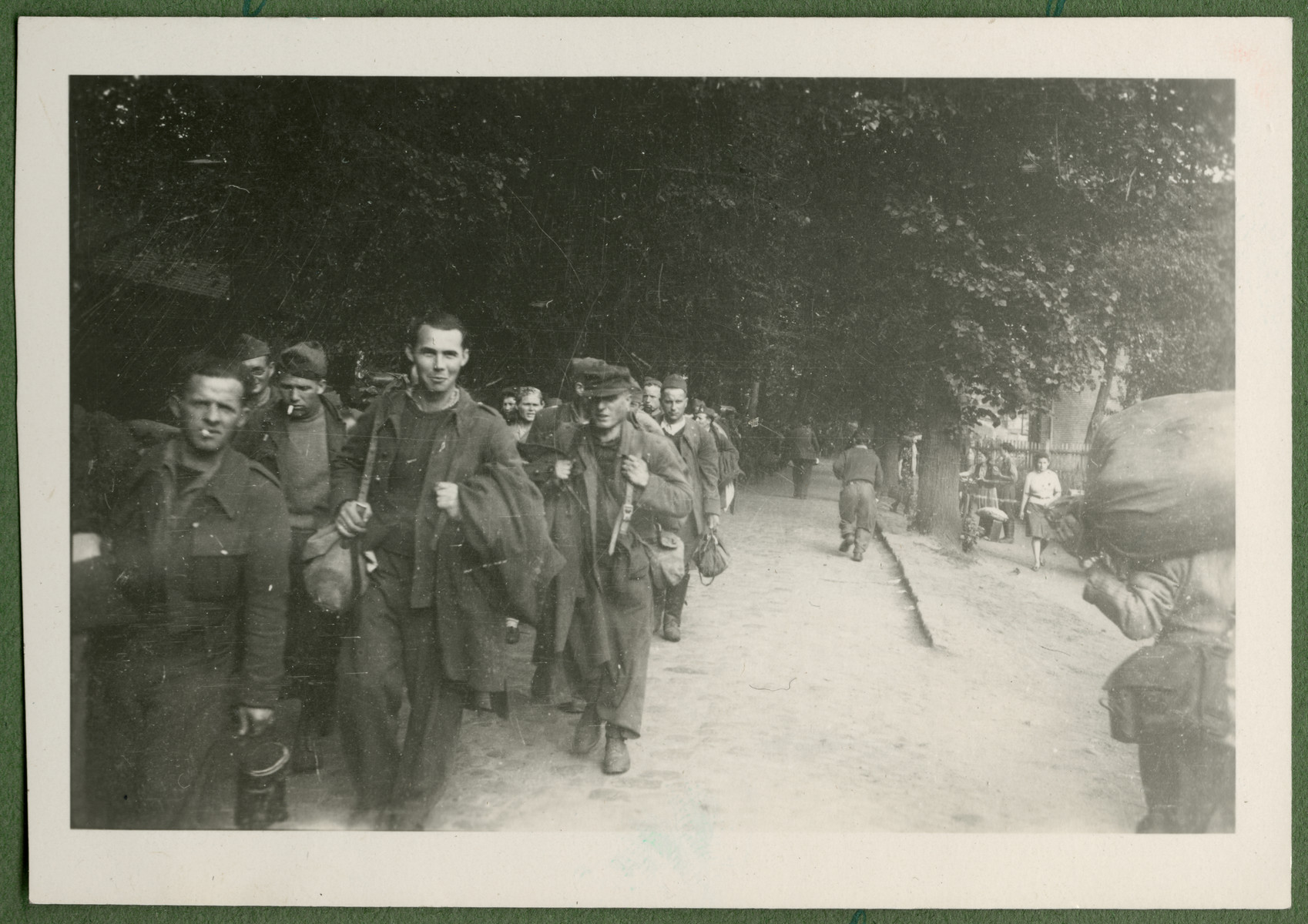 A column of former French prisoners marches down a road in Germany on their return to France.