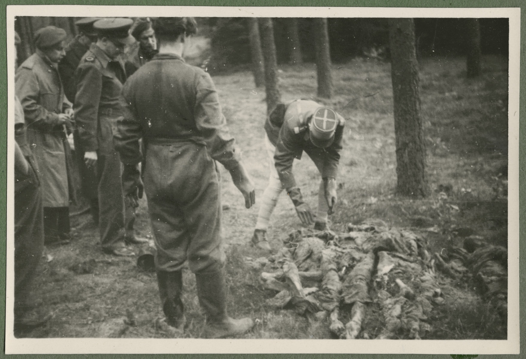 Under the supervision of British troops, German civilians and Nazi officials exhume the corpses of 243 slave laborers for proper reburial.  The victims were shot by their guards on the railway lines at Lueneburg on the way to the Belsen Camp.