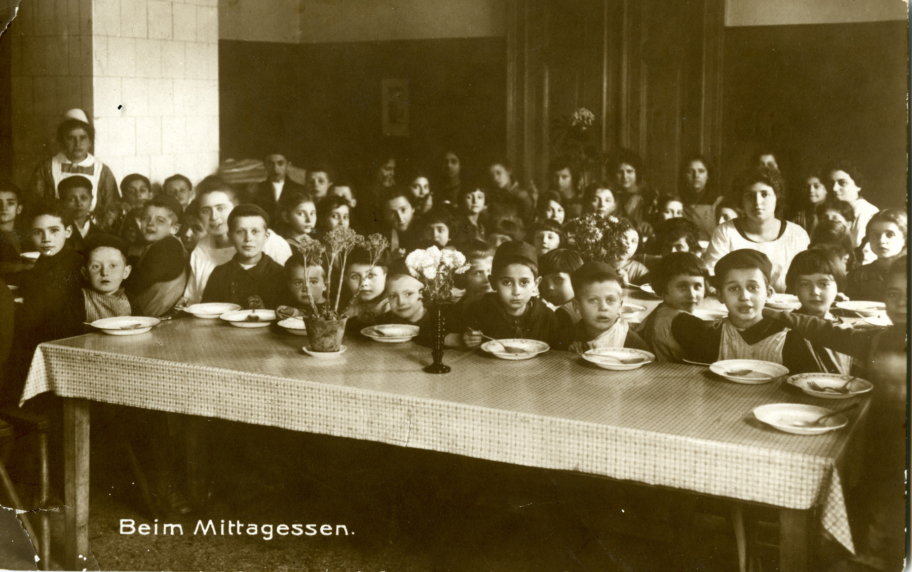 Lunches at Beith Ahawah Children's Home. Beate Berger is standing in the back left corner, in nurses' uniform.