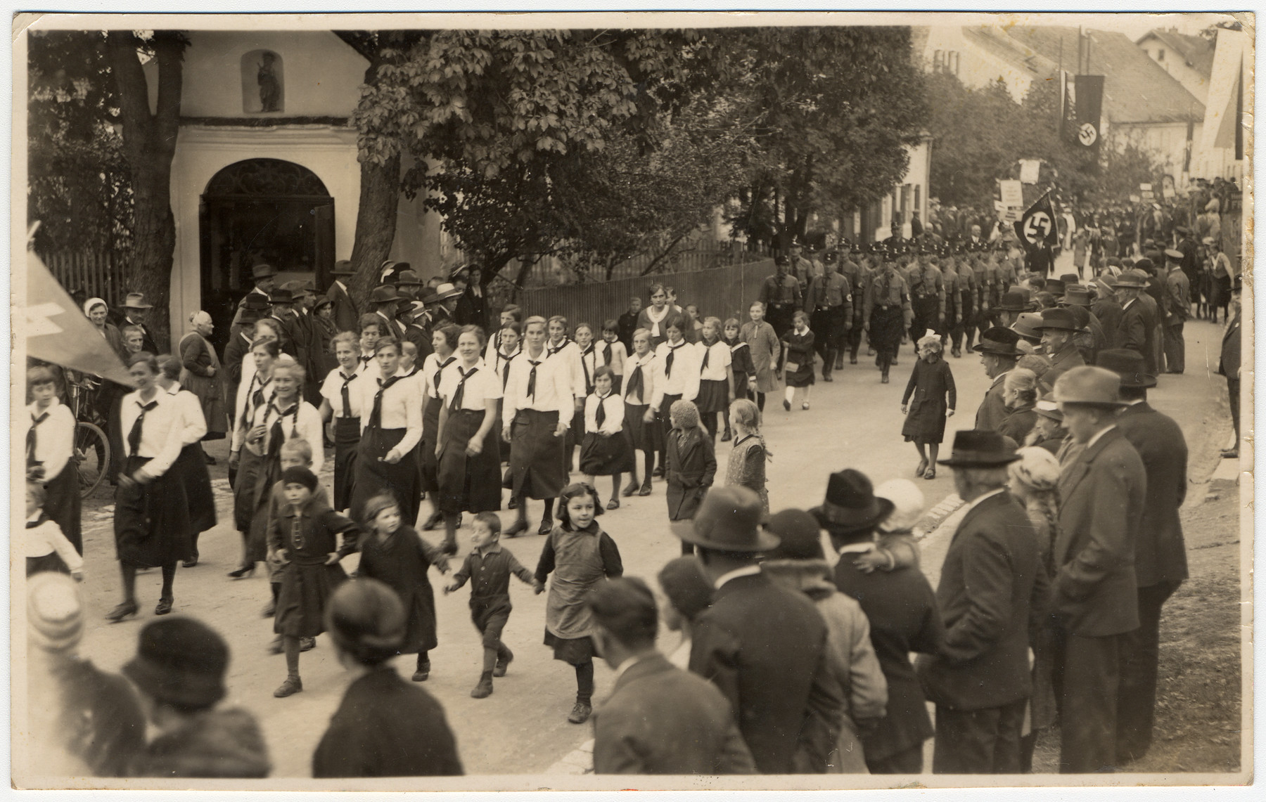 Members of the BDM walk proudly down the street of a German (?) town.