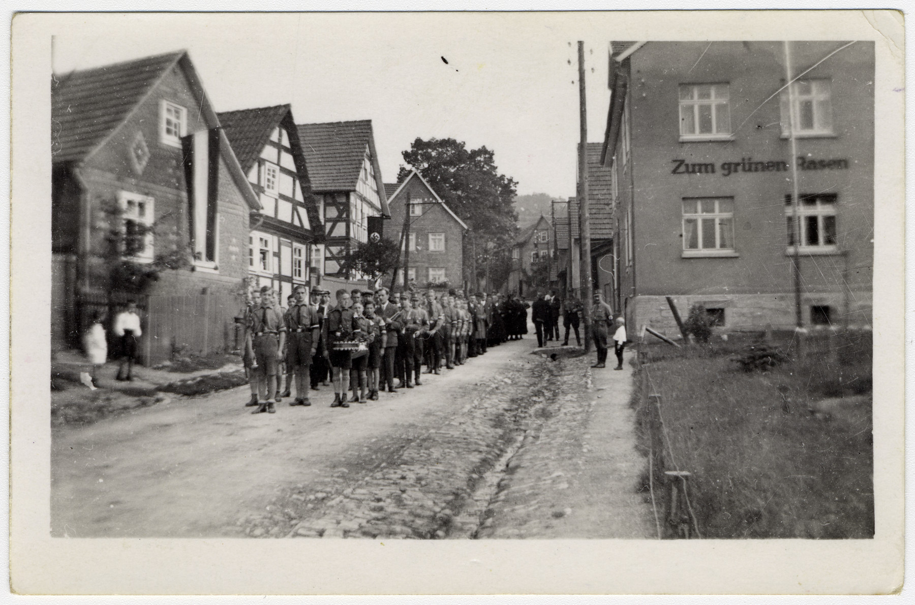 Members of the Hitler Youth stand ready to parade down a street.