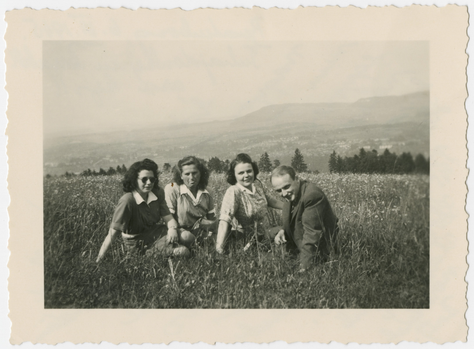 Four young people who had come to Switzerland on the Kasztner transport pose in a grassy field.  Eva Weinberger is seated second from the left.  Berta Davidovitz is pictured second from the right.  The inscription reads: Dear Eva: I am sorry I wasn't able to be with you on vacation.  I'm sending you this picture as a remembrance of three friends from Kibbutz Hamarichot.  I was with them in Bern on May 20, 1945. From your friend, Berta