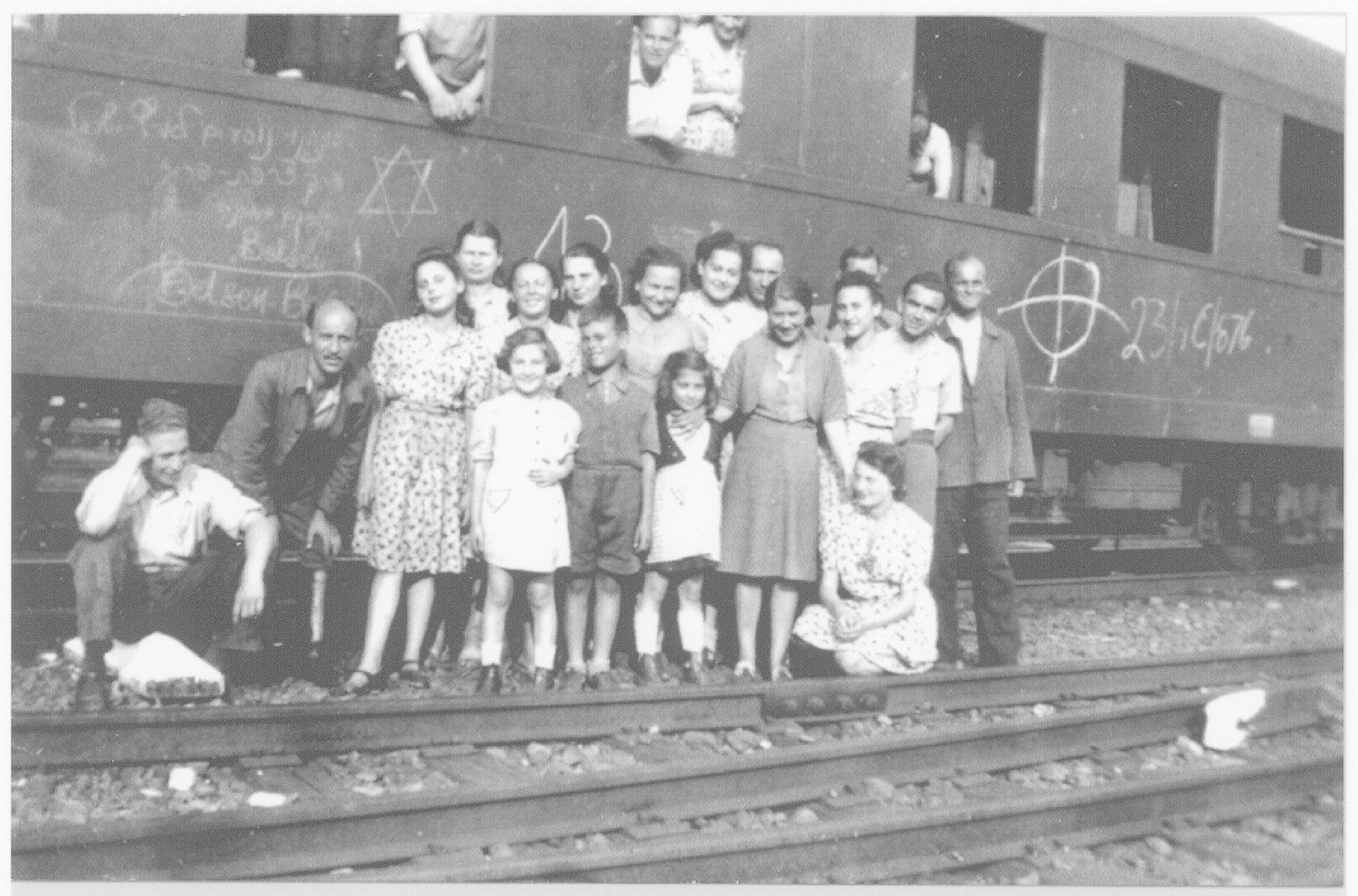 """Prisoners from an evacuation train from Bergen-Belsen pose next to a railroad car in Magdeburg.    This photo was probably taken  a few days after liberation since written on the side of the car is """"Bergen-Belsen"""" and """"We are going to Israel by way of France.""""  Pictured are the donor's stepfather, Chil Elbaum (back center), Maurice (second from the right), Esther (standing third from the right) and Chaim Elbaum (sitting on the far left)."""