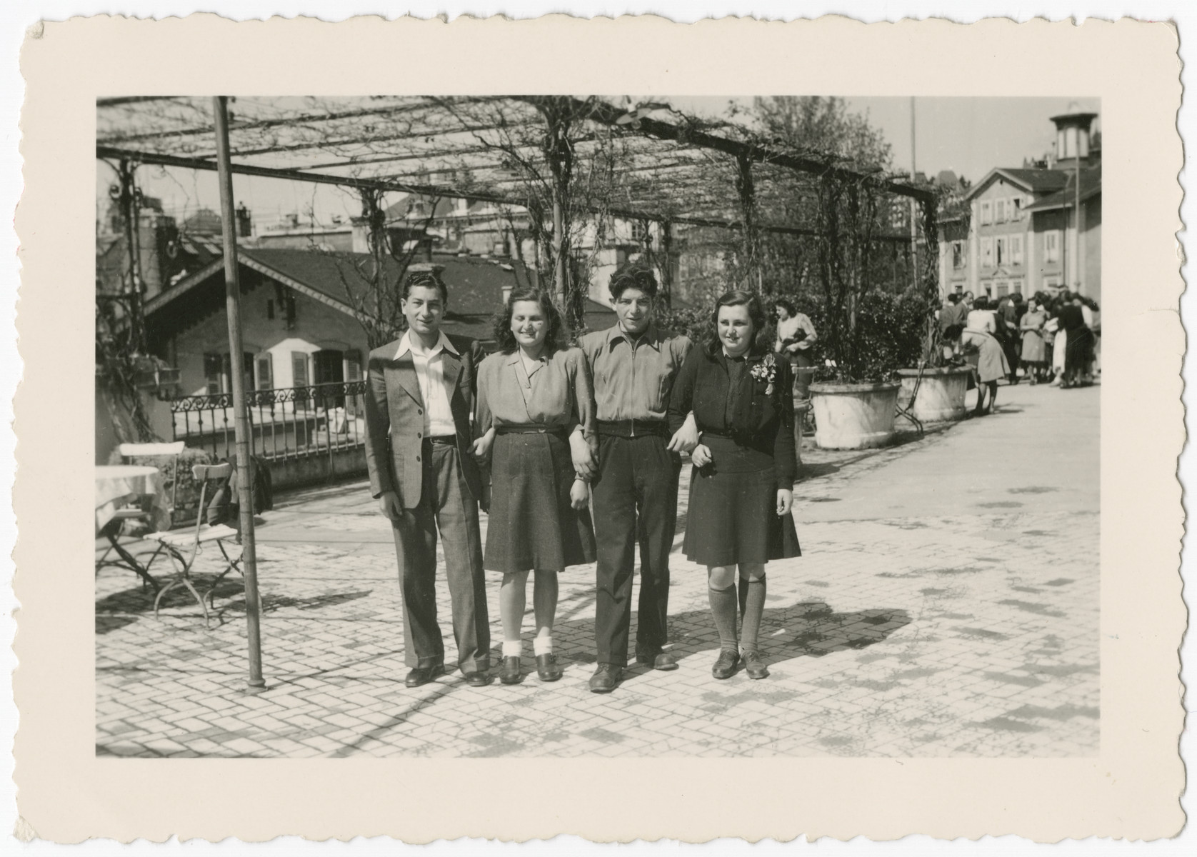 Four young people pose together on a street in Montreux, Switzerland after arriving on the Kasztner transport.  Pictured from left to right are Shlomo, Eva Weinberger, Menachem Weingarten and Gitel (from Chust).