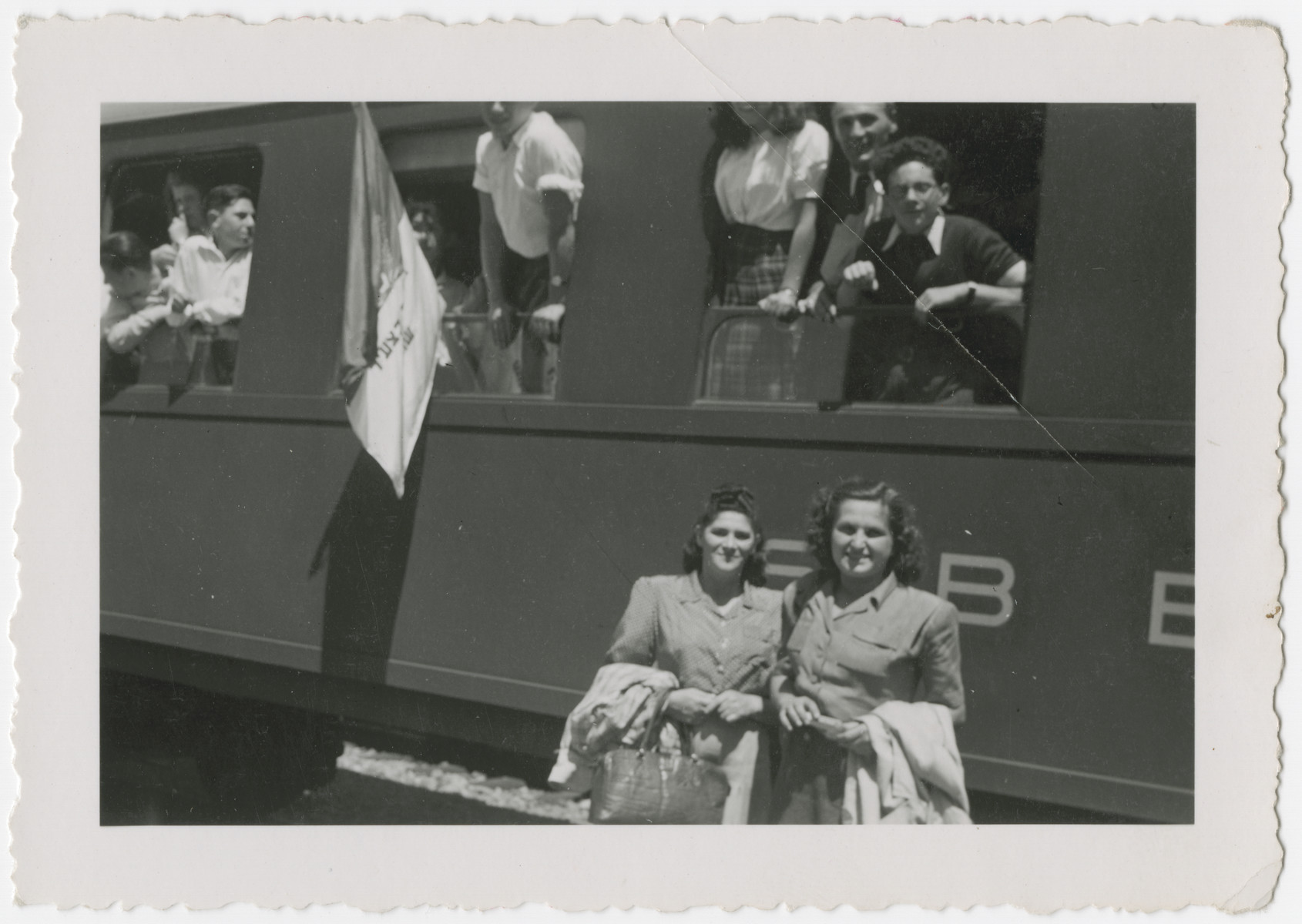 Hungarian Zionists who had come to Switzerland with the Kasztner transport pose inside and outside a train adorned with a Zionist flag.  Eva Weinberger is pictured in the front right, and Rosa Schiff is in the front left..