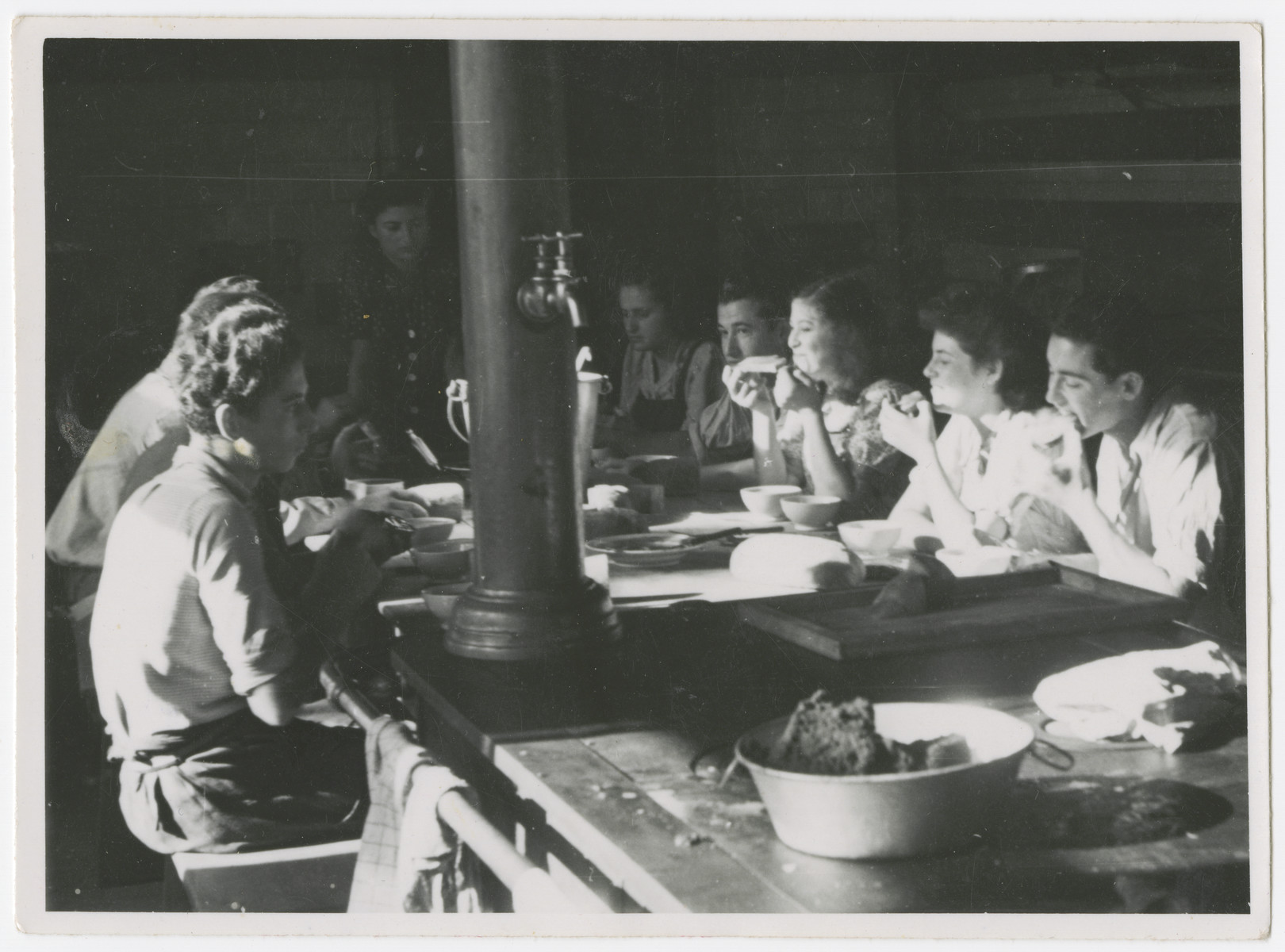 Zionist youth, some who came to Switzerland on the Kasztner transport, share a meal in the dining room of a kibbutz hachshara near Bern.  Eva Weinberger is pictured sixth from the right.
