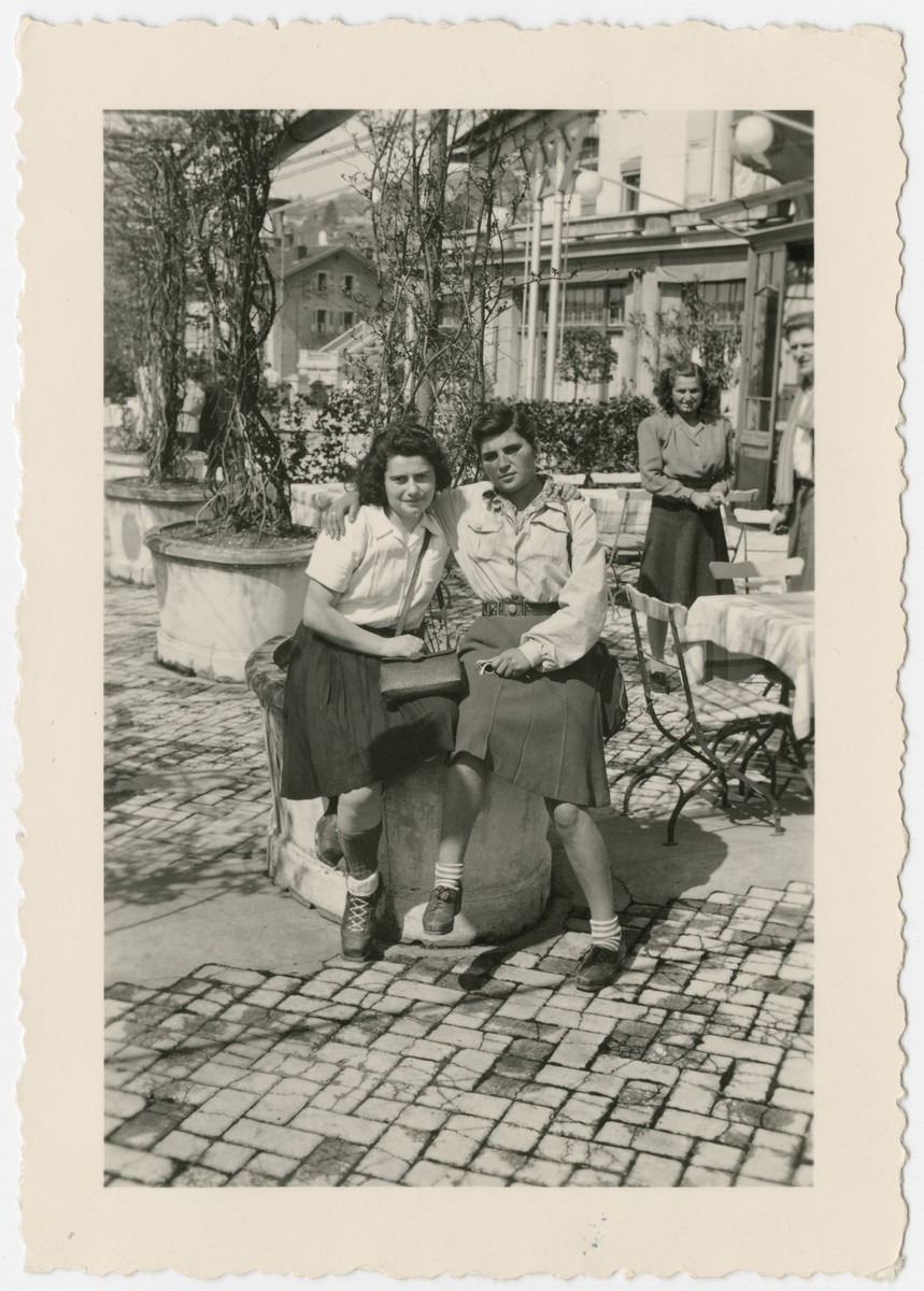 Two women who came to Switzerland on the Kasztner tranport pose together at an outdoor cafe.  Pictured in front are Berta Rubinsztajn (left) and ? Moskovitz (right).  Eva Weinberger is standing behind them at the back right.