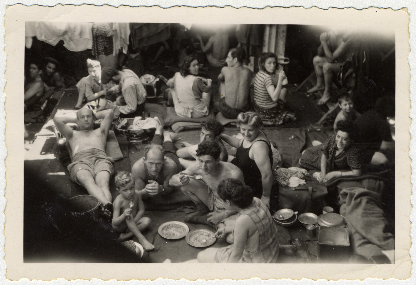 Passengers on board the Exodus relax and eat a meal while en route to Palestine before the British navy intercepted the ship.  Pictured on the far right wearing a dress and leaning on her side is Frances Kanenberg.