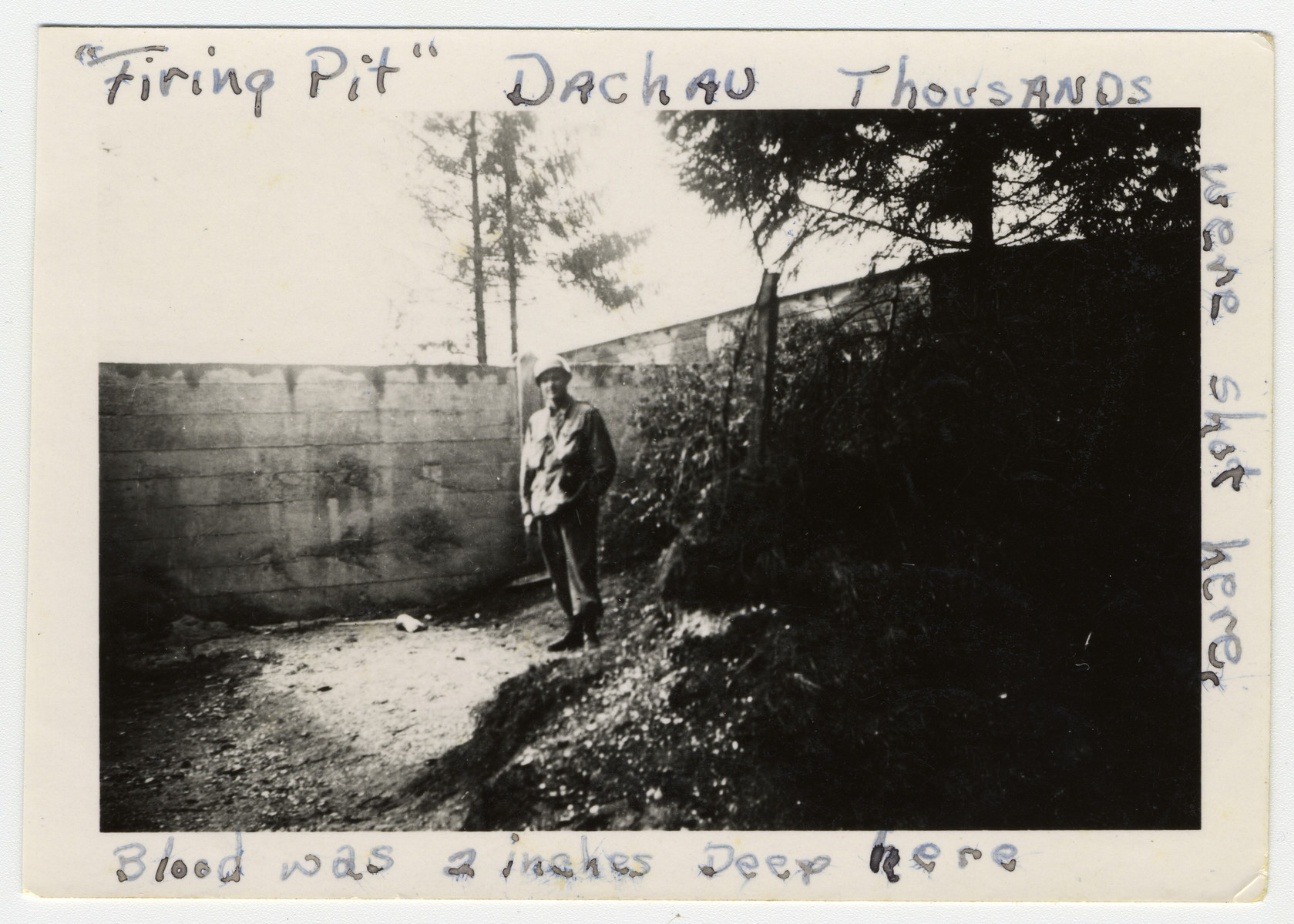 """An American soldier stands next to a wall where prisoners were shot in the Dachau concentration camp.  The original caption reads """"Firing Pit Dachau -- Thousands were shot here.  Blood was two inches deep here."""""""