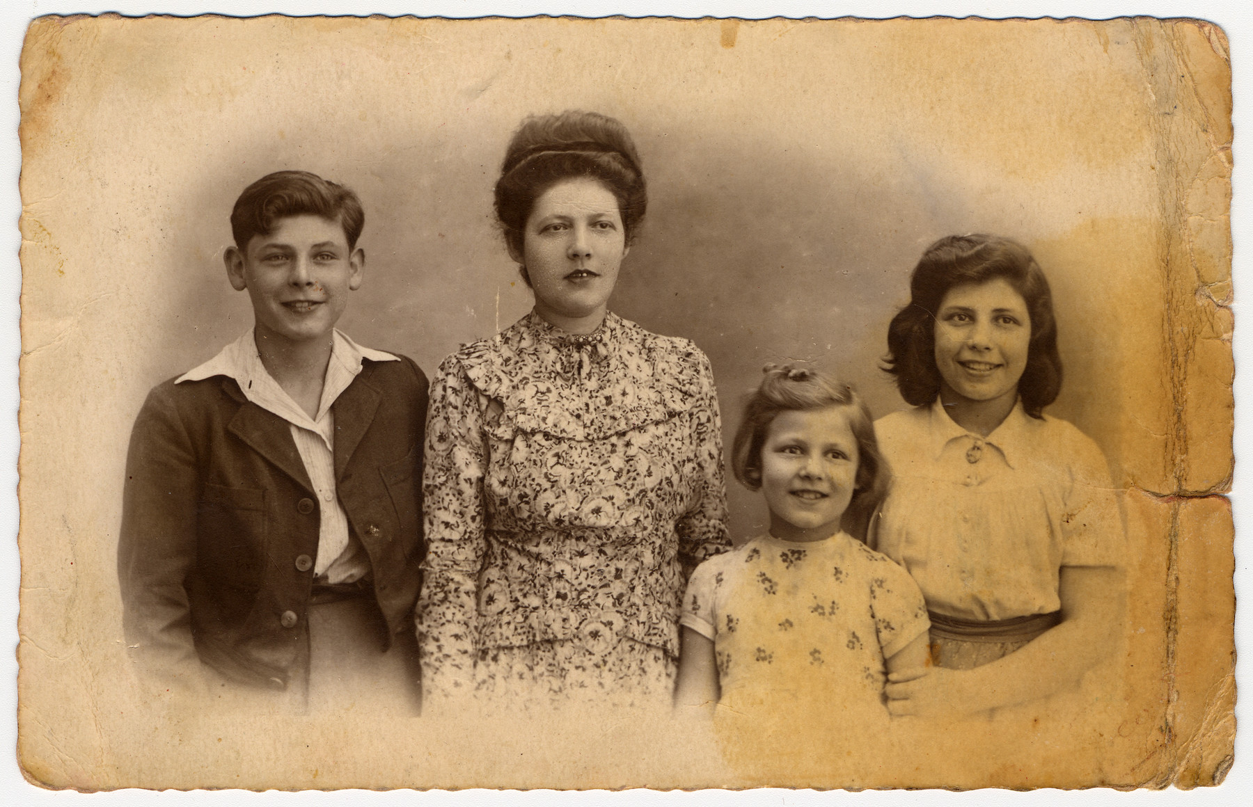 Postwar portrait of a Jewish woman and her three children, all of whom survived the war in hiding.  From left to right are Aime, Lola, Monique and Irene Burenstein.