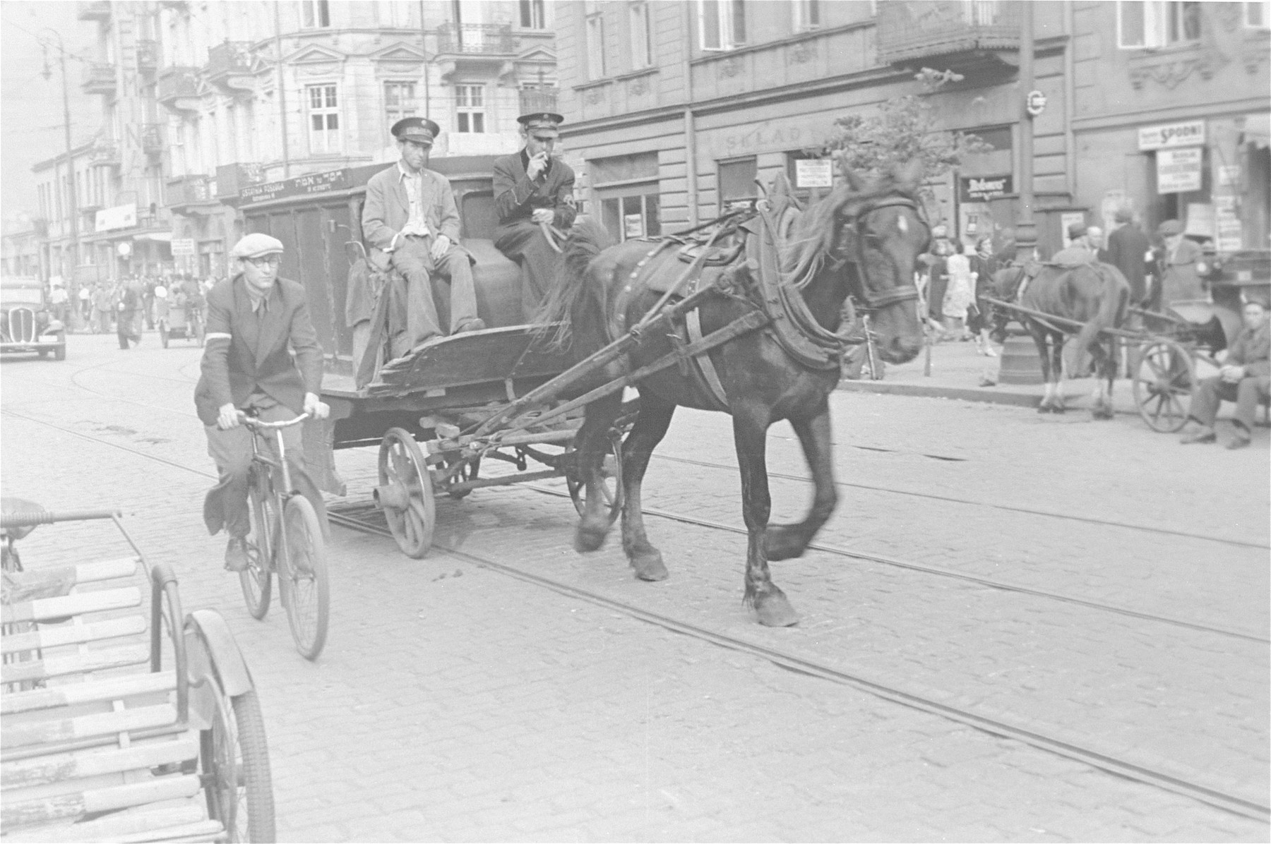 Undertakers drive a horse-drawn funeral wagon through the streets of the Warsaw ghetto.