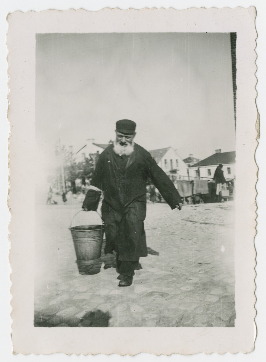 An elderly Jewish man carries a bucket in an unidentified ghetto.