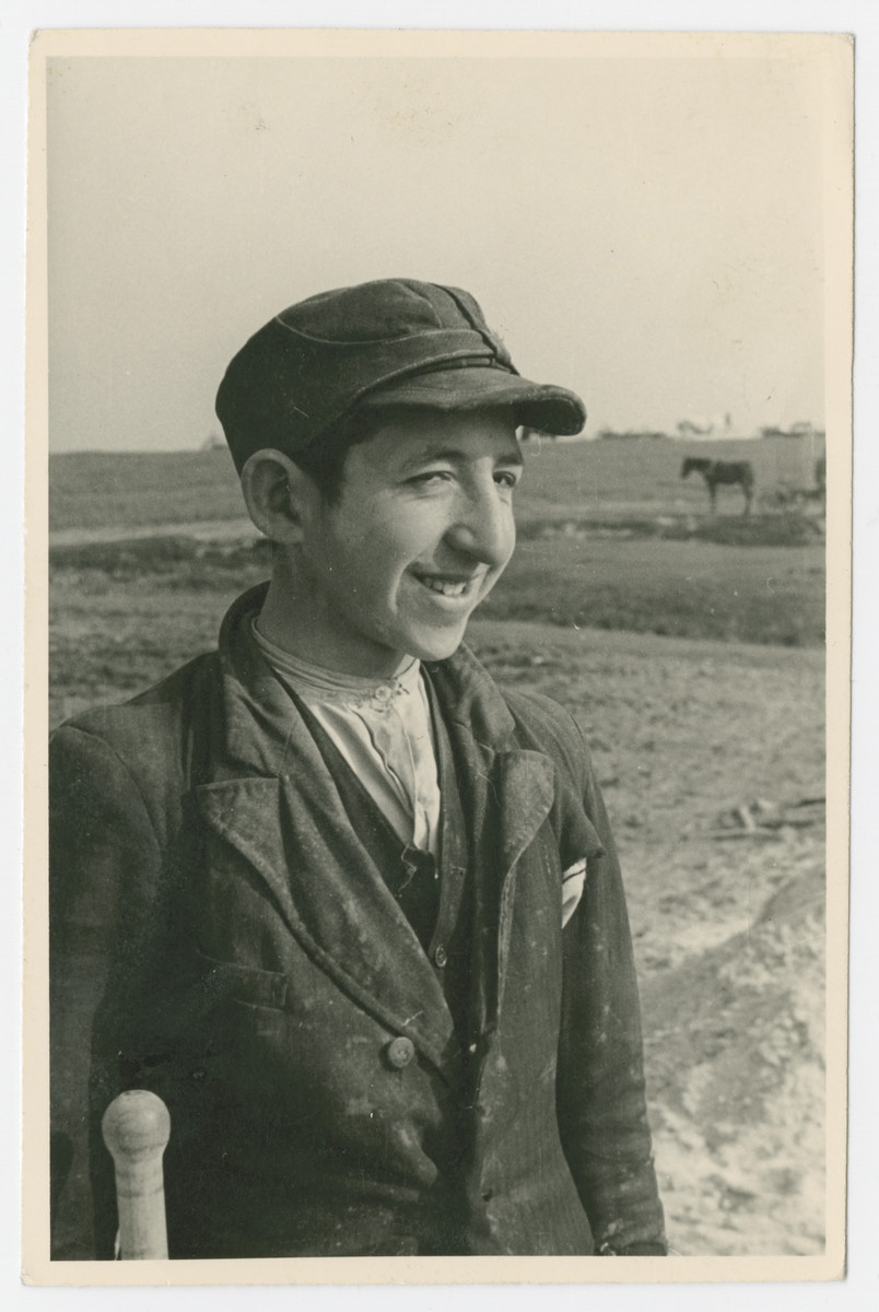 A young Jewish man stands in a field.