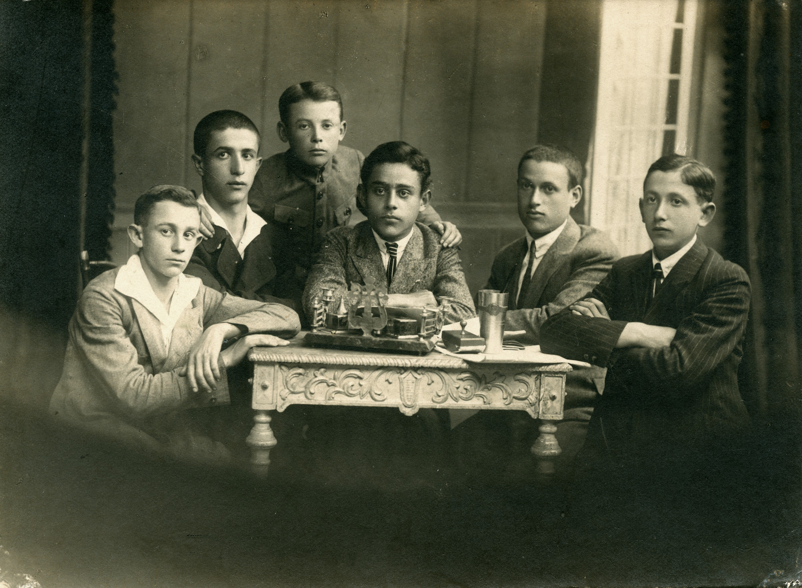 A photo of six young boys sitting and standing aroung a table. Feivel Frankfowicz is on the far left and his friend Lubici Weinstein is in the middle.