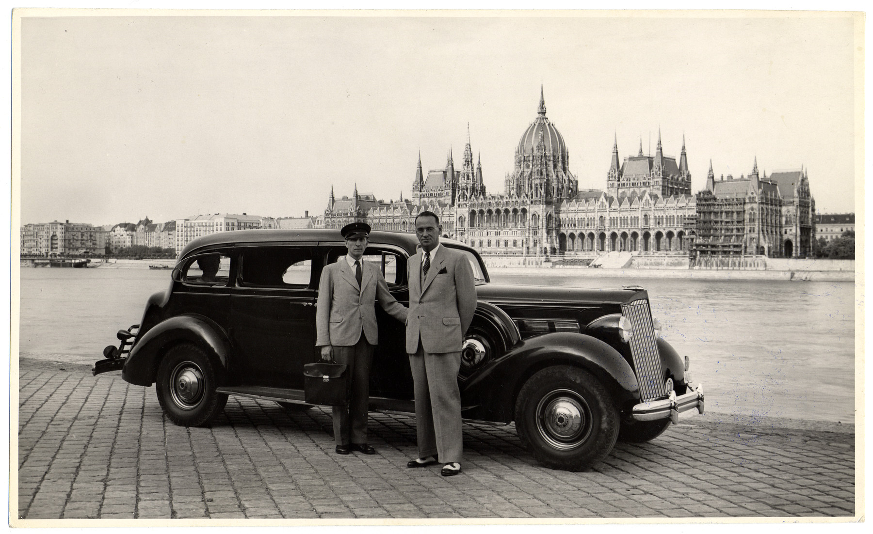 Swiss Consul General, Carl Lutz, poses with his driver, Charles Szluha, along the bank of the Danube River across from the parliament building in wartime Budapest.