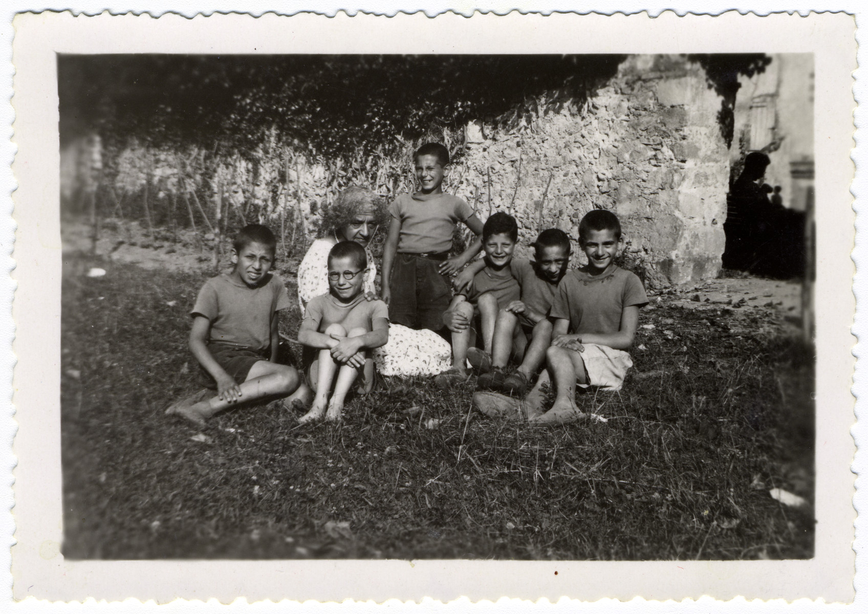 A group of children sit with their female guardian at the children's home Chateau de la Hille.   Pictured are the teacher Irene Frank is surrounded by, from left, Guy Haas, Joseph Findling (?), Manfred Templer (?), Paul Schlesinger, Gerhard Eckmann and George Herz. Eckmann was deported, survived Auschwitz and was murdered in Lieberose, Germany, in early 1945.
