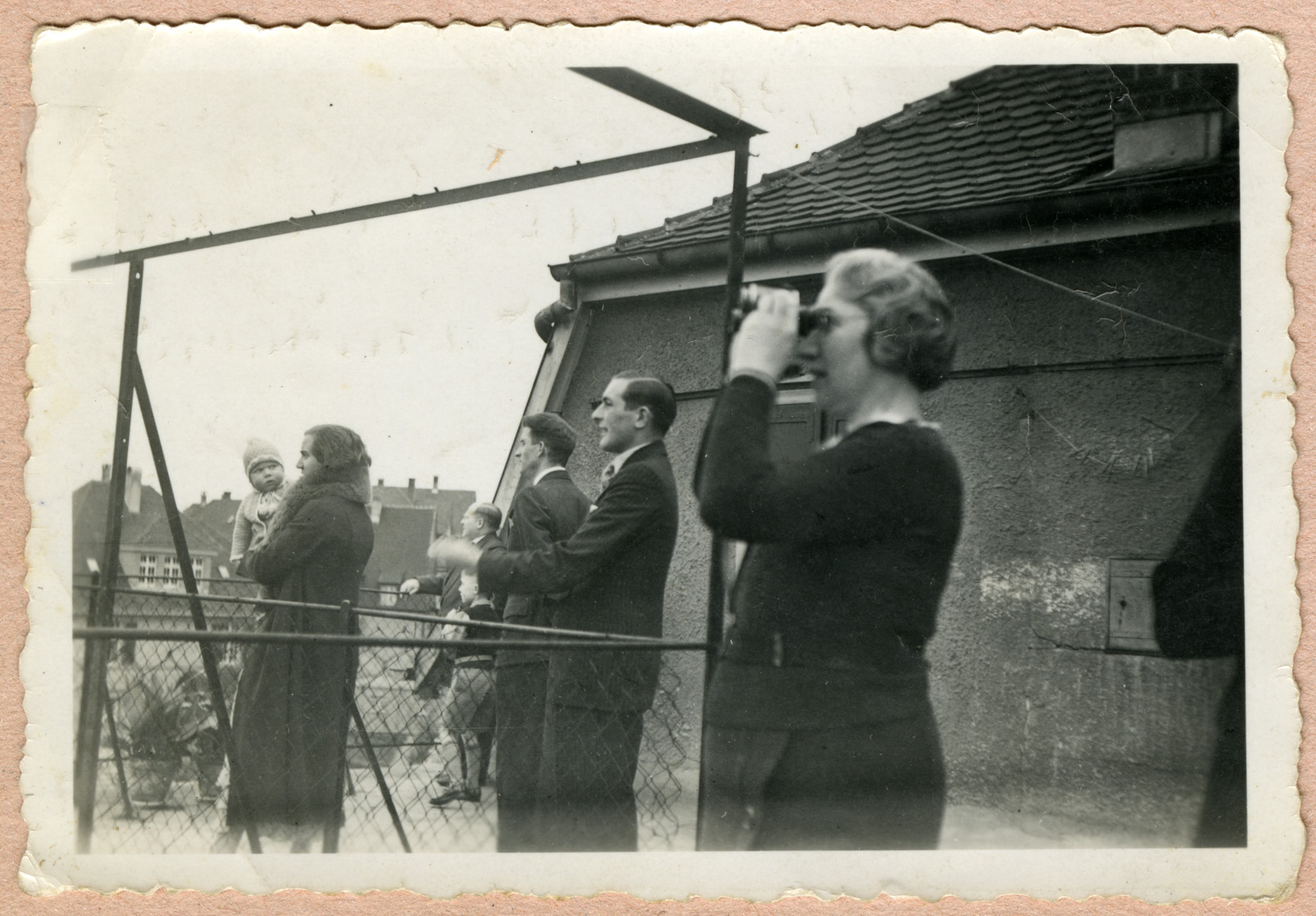 Claire Feigenbaum looks up to the sky with binoculors.  [Date and location are not verified.]