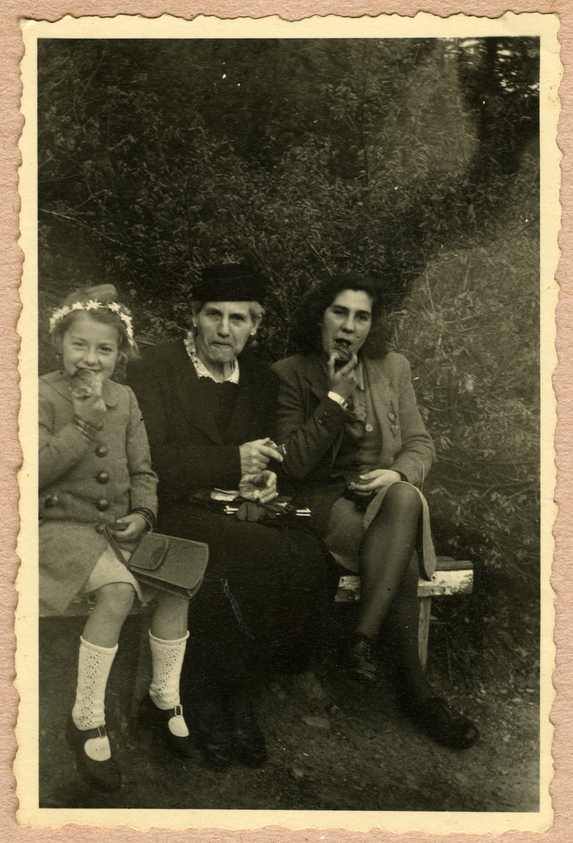 Olga Alt sits on a park bench and enjoys a snack flanked by her two daughters.  Margot Alt is on the right, and her younger sister Dora is on the left.  Olga and Dora were killed in an air raid shortly after this photograph was taken on April 3, 1945.