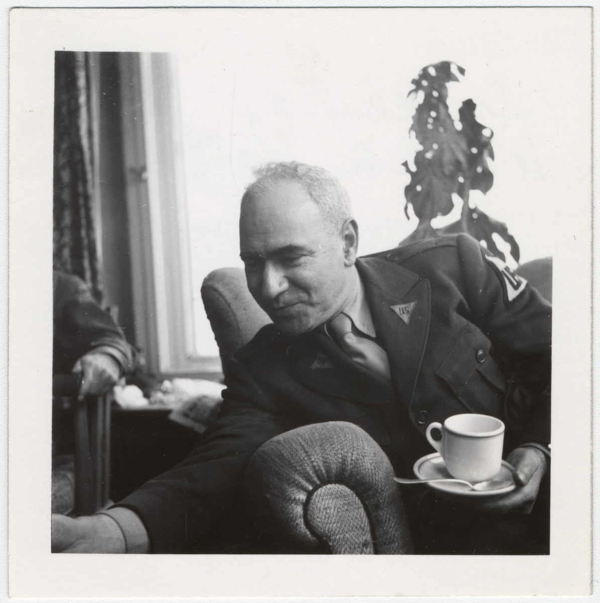 Close-up portrait of Maurice Levitt holding a coffee cup in the UNRRA House in Lindenfels.