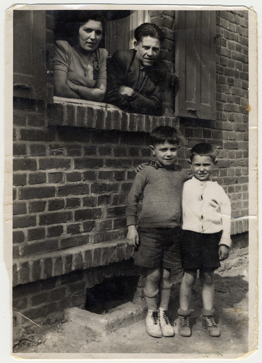 Shanke and Shlamke Minuskin look out the window of their quarters in the Zeilsheim displaced persons' camp while their two boys, Henik and Kalman, stand below.