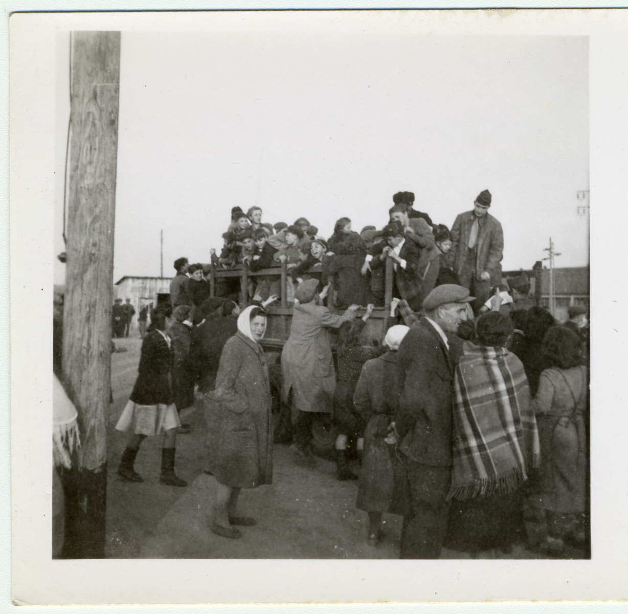 "A group of children from a displaced persons crowds onto a truck.  David Marcus' original caption reads: ""'Sorry, standing room only, you better wait for the next trip.'"""