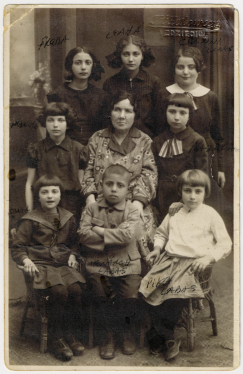 Portrait of Rifkeh-Rochel Orlinsky surrounded by her grandchildren.  Pictured are: (front row, left to right) Sonia, Henach and Pinka.  (middle row) Marsha, Rifkeh-Rochel Orlinsky, and Razal.  (top row) Frida, Leah and Chana.