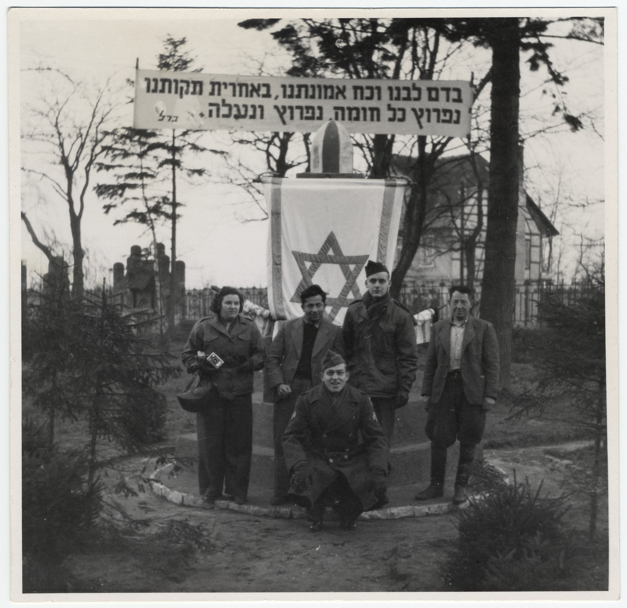 """Five people, including members of the Frankfurt Jewish GI Council pose in front of a memorial in a German displaced persons' camp.  Crouching in front in Asher Hirsh, a German Jewish refugee who joined the US Army.  The Hebrew banner reads: """"With the blood of our hearts, and the strength of our faith, with our last hopes, we will breach every wall, breach and ascend."""""""