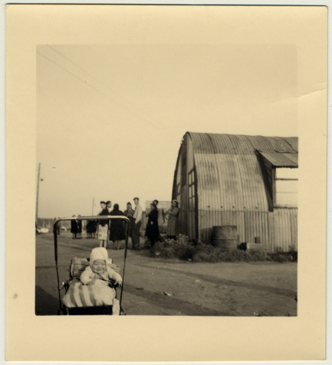 """A young baby sits in its carriage next to a Quonset hut in Babenhausen.  David Marcus' original caption reads: """"Quonset huts served as housing for up to 25 people or four or five families."""""""