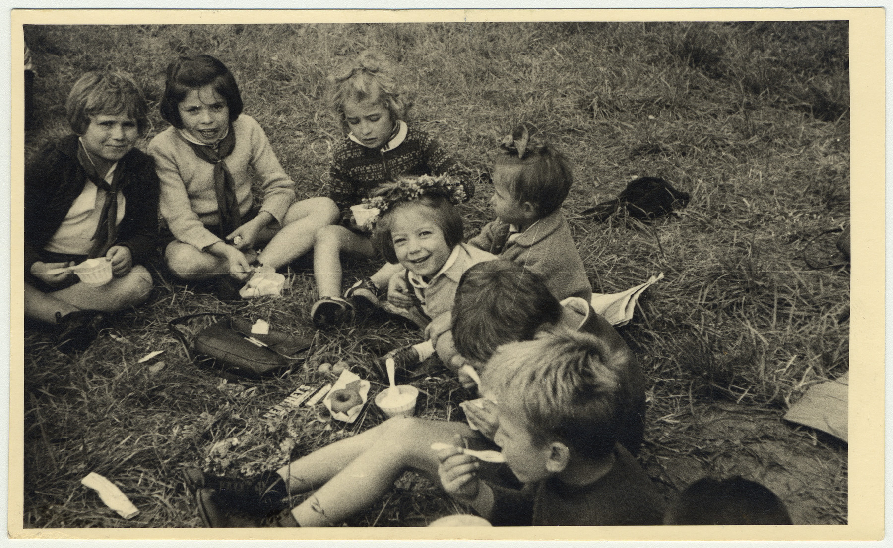 "Young children enjoy an ice cream picnic.  David Marcus' original caption reads: ""Ice cream, dougnuts, and happy faces."""