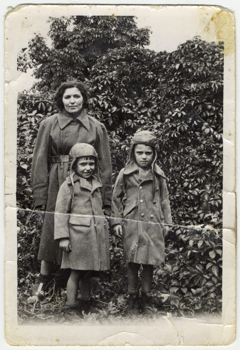 Shanke Minuskin stands outside in the Zeilsheim displaced persons' camp with her two sons, Kalman and Henik.  The boys are wearing coats their mother sewed for them in the forests made from the coat of a dead German.