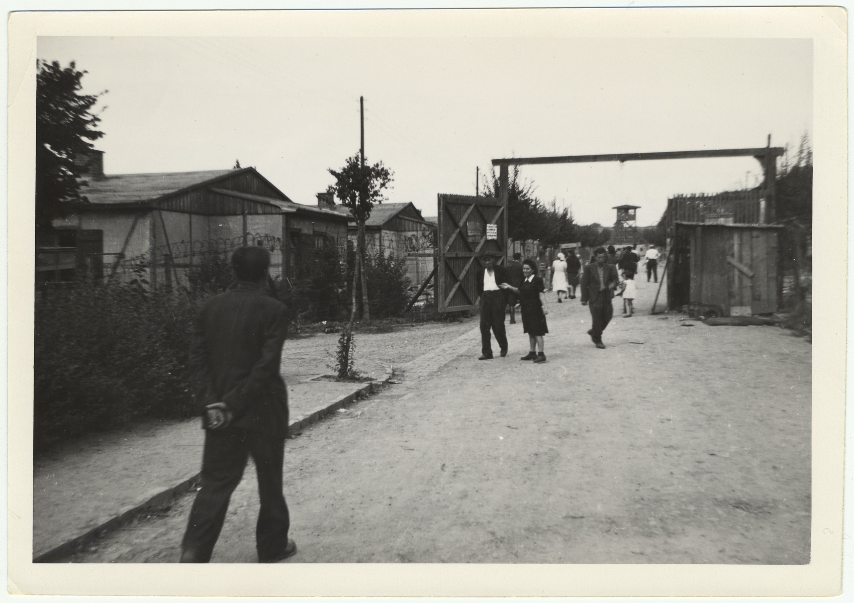 Displaced persons walk down the main street of their camp, probably a former concentration camp.  A watch tower can be seen in the background and barbed wire on the sides.