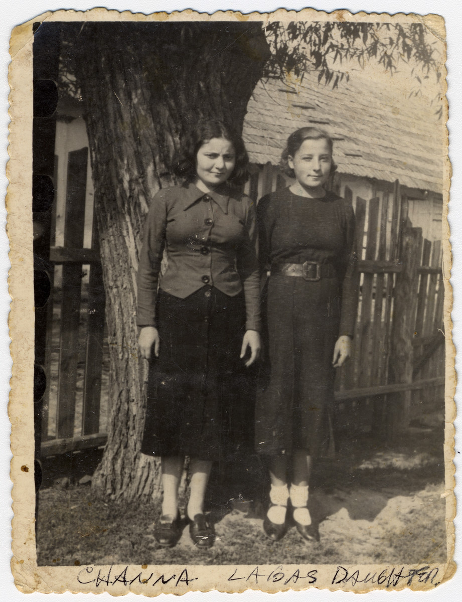 Two young women stand outside by a fence in Zhetel, Poland.  Pictured are Chaike Orlinsky (Leibe's daughter) and a friend.