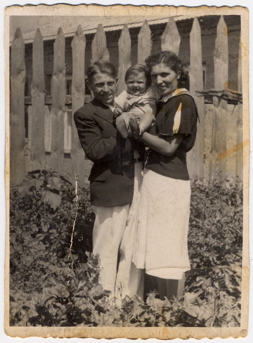 Shlamke and Shanke Minuskin pose with their baby son, Henikel, in the garden of their home.