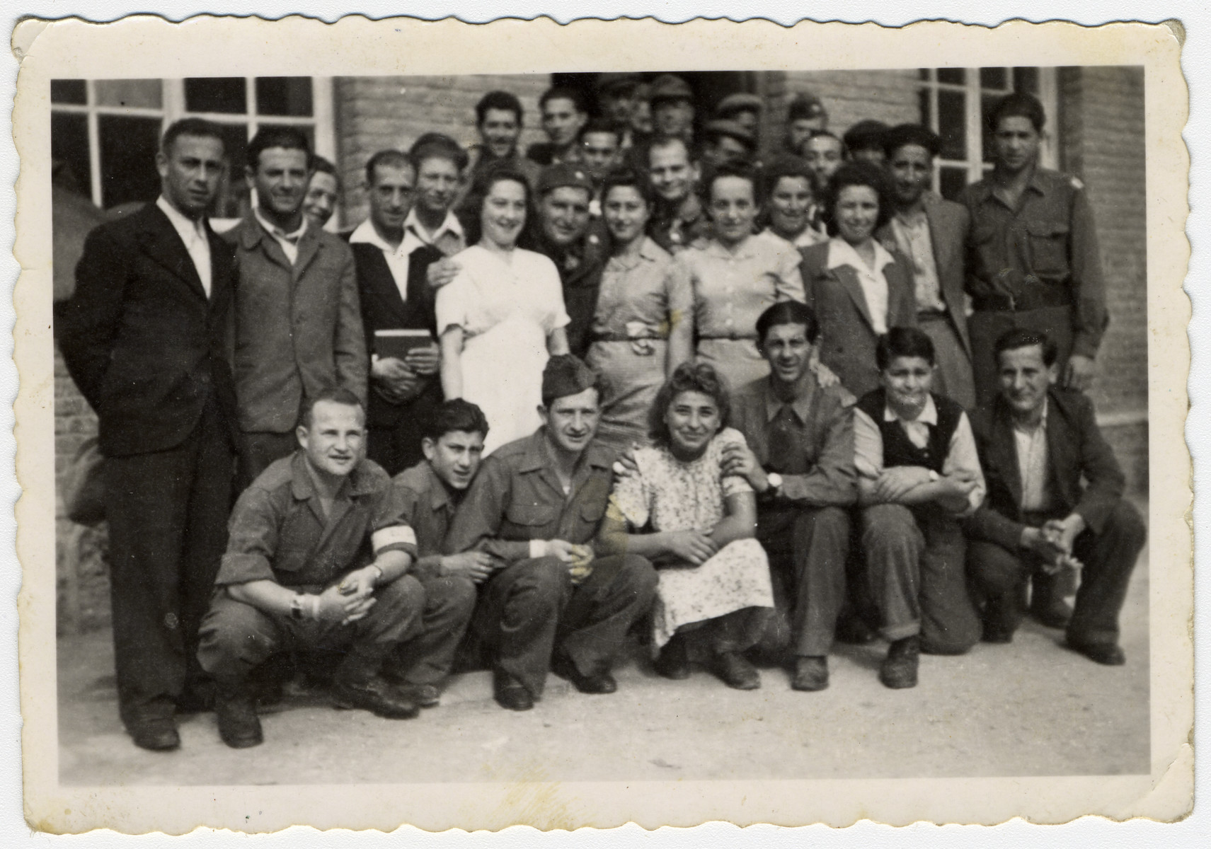 Group portrait of Jewish DPs and American Jewish soldiers at a displaced persons camp in Salzburg.  Among those pictured is Hadasa Werdygier (second row from the front, wearing a white dress).